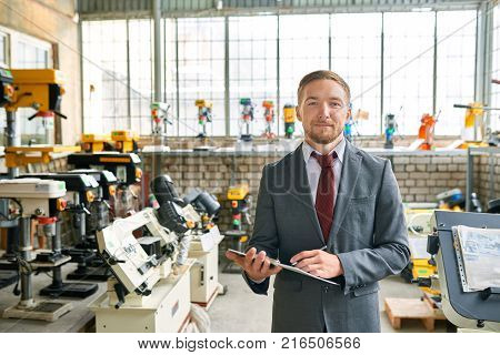 Portrait of successful sales assistant wearing suit posing smiling confidently at camera, standing in showroom selling industrial machine tools