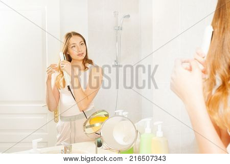 Attractive young woman with straight hair using flat iron to create curls or waves, seen in the bathroom mirror