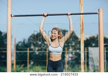 Young slender fitness woman tightening on the turret