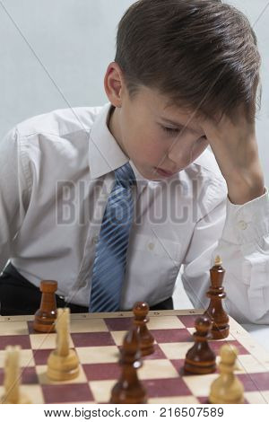 Young chess player ponders stroke, his head tilted over a chessboard