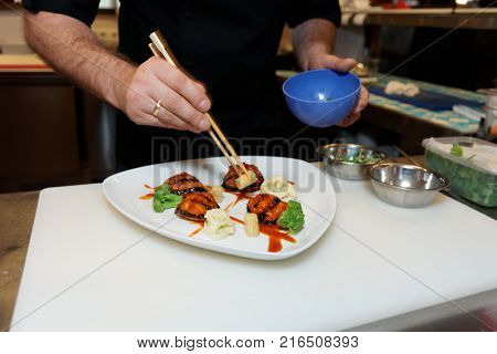 Chef is decorating fusion style dish using chopsticks, copy space