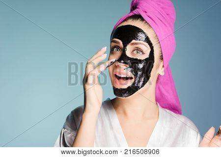 happy young girl wants clean skin, applies a black cleansing mask on face