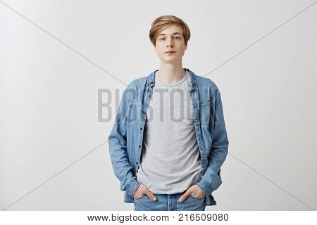 Portrait of pensive young fair-haired guy with blue eyes wears denim clothes, keeps hands in pockets, looks confidently at camera, holds hands in pockets, poses indoors