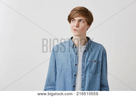 I don't know. Headshot of doubtful caucasian young male wearing denim shirt, pouting lips and looking up with indecisive expression on his face, showing doubt and hesitation. Body language and face expression