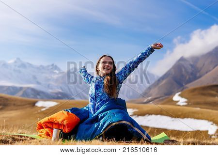 an active young girl in a blue jacket travels along the Caucasian ridge, enjoys clean air, sits in a sleeping bag