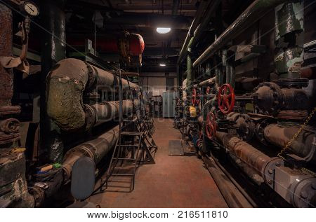 Old vintage control center in the boiler room with tubes and round water taps
