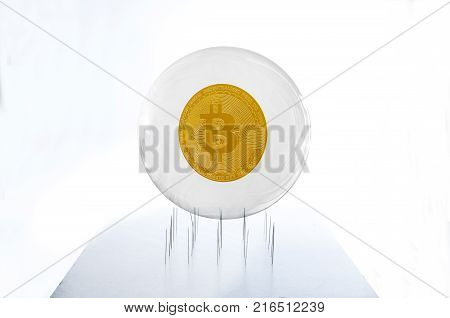 Bitcoin inside a bubble over a needles bed simulating the fragility of this speculative currency