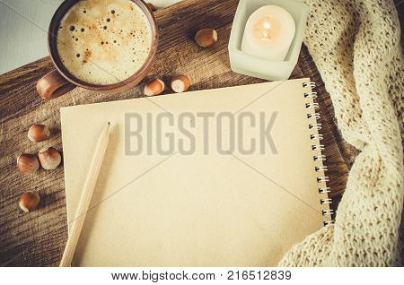 Winter and autumn composition. Vintage notebook with pencil candle and cup of coffee and knitted white plaid or scarf. Top view. Write your plans and wishes on christmas holidays.