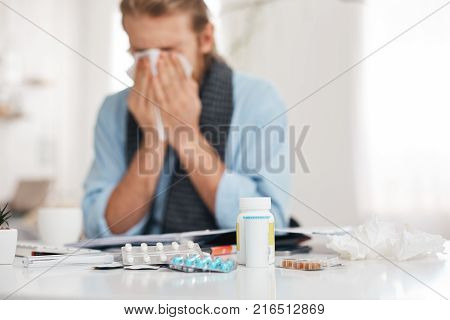 Portrait of ill, sick bearded male sneezes and coughs, uses handkerchief, rubs nose. Man has running nose, caugh, bad cold, sits at work place, surrounded by pills, drugs, and vitamins.