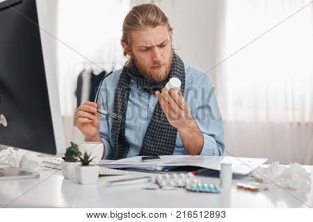 Ill bearded male office worker in blue shirt and scarf with spectacles concentrated on reading prescription of pills. Young manager with flu, sits at workplace surrounded by pills, tablets, vitamins and drugs. Health problems