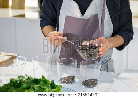 Chef's hands prepare chia pudding in the white kitchen. Health and super food to boost immune system or bodycare concept