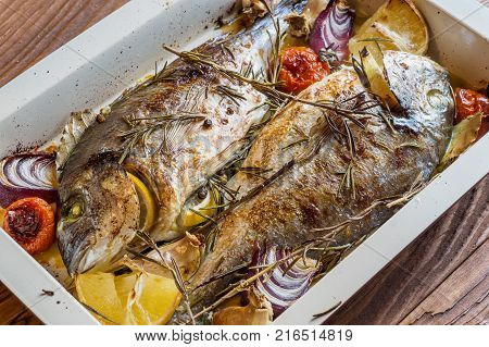 Two delicious whole baked fish. Baked dorado with lemon onions rosemary cherry tomatoes and spices on a wooden background. Delicious roasted dorado on oven tray. Diet and healthy food. Top view.