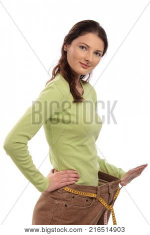 Teenager girl wearing several sizes too big trousers, holding it up with hand, using measuring tape as belt, looking at camera, smiling. Cut out, isolated on white.