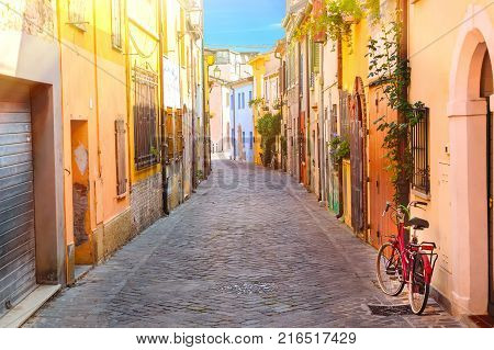 Narrow street of the village of fishermen San Guiliano with colorful houses and a bicycle in early morning in Rimini Italy.