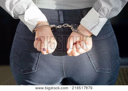 Close-up. Arrested woman handcuffed hands at the back. Prisoner or arrested terrorist close-up of hands in handcuffs selective focus.