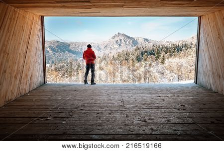 Man stay in big wooden hangar and looks on snowy mountains