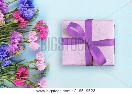 Cornflowers and gift box on blue background