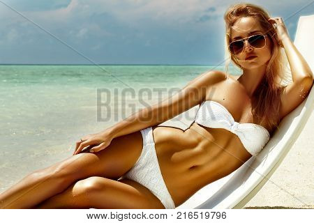 Summer girl model with tanned sexy body. Posing in the white chair on the beach of the tropical island.