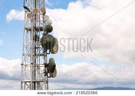 Transmitters And Aerials On Telecommunication Tower With Cloudy Blue Sky