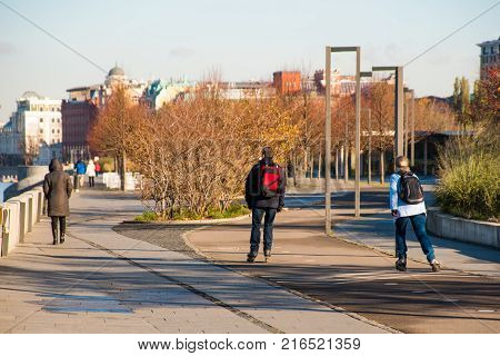 Happy couple roller blading together in public city park