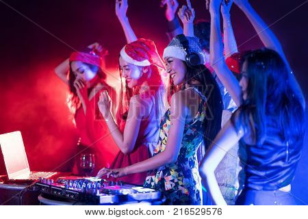 Portrait of group of friends dancing with active pretty young DJ woman playing music on laser lighting background.