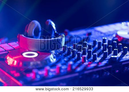 In selective focus of Pro dj controller.The DJ console cd mp4 deejay mixing desk Ibiza house music party in nightclub with colored disco lights.