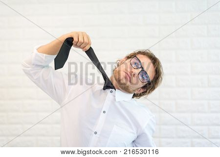 CrazyBearded Businessman Holding His Tie Hanging Himself against White Block Background.In A Moment Of Despair