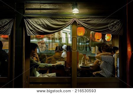 KYOTO, October 18, 2016: DINNER AT LOCAL RESTAURANT. Some customers sit next to counter, others sit elsewhere. A couple sat by the window have finished the meals and been waiting to pay their bills.