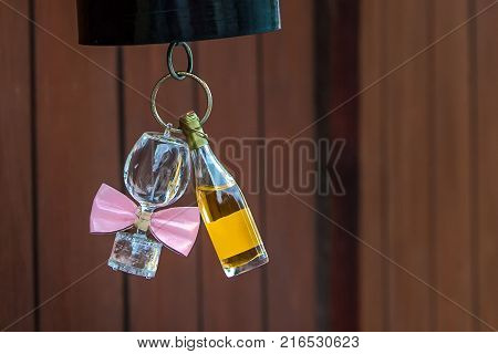 Still life - bottle of wine and wine glass. A bottle of wine, and a wine glass with pink bow tie attached are hung to the bottom of red paper lampshade.