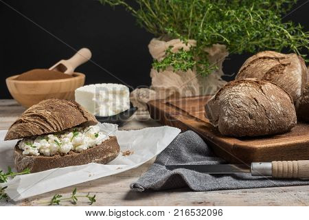 Homemade farm bread with cottage cheese curd and thyme herb malt flour and curd cream in bowl on wooden table.
