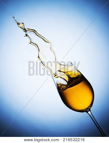 splash of white wine from goblet on a blue background