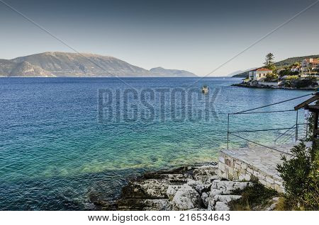 Panoramic view of the bay of Fiskardo boat sailing and finally the mountains of Kefalonia island Greece