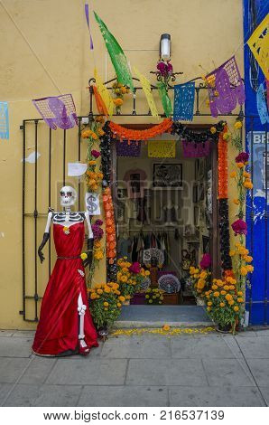 OAXACA, OAXACA, MEXICO- OCTOBER 30, 2017: Skull  with a red dress outside of a store as decoration for mexican Day of the Dead celebration in Oaxaca, Mexico