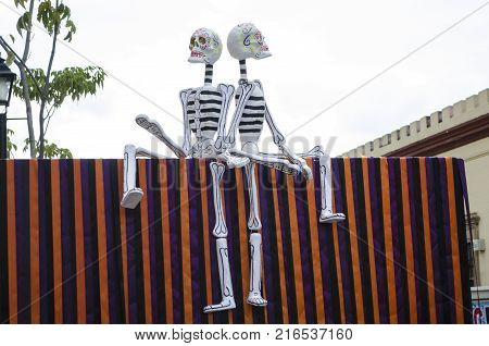 OAXACA, OAXACA, MEXICO- OCTOBER 30, 2017: Skulls sitting on a colorful wall as decoration for mexican Day of the Dead celebration in Oaxaca, Mexico