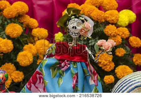 OAXACA, OAXACA, MEXICO- NOVEMBER 1, 2017: Little skull dressed with traditional clothes and yellow flowers, part of a mexican Day of the Dead offering altar