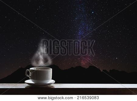 Cup of hot drinks on the table with beautiful Milky Way with silhouette mountain ride. Milky Way sightseeing at night poster