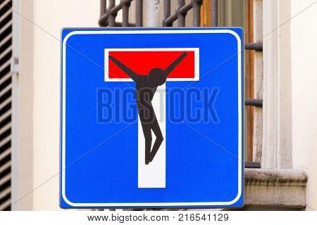Road sign with a crucified man street art metropolitan art