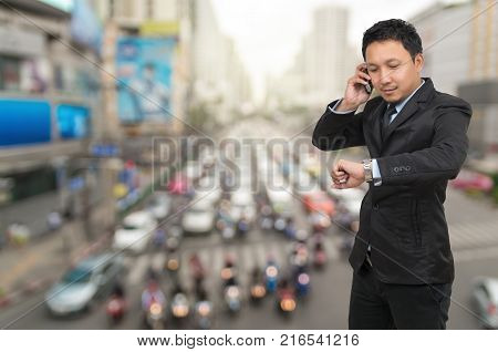Young businessman talking on mobile phone and looking at watch on abstract Blurred photo of traffic jam with rush hour business rush hour concept