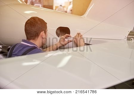 Airplane detail attachment. Man is attaching a detail to an airplane.