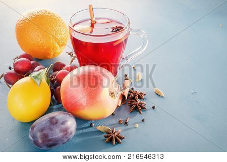 Winter alcoholic drinks - mulled wine, punch, grog. Glass jars with mulled wine. Hot fruit tea. Spices, fruit. Hot wine. Place for text