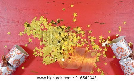 Festive surprise concept, opening a Christmas cracker bon bon with gold glitter stars on rustic red wood table.