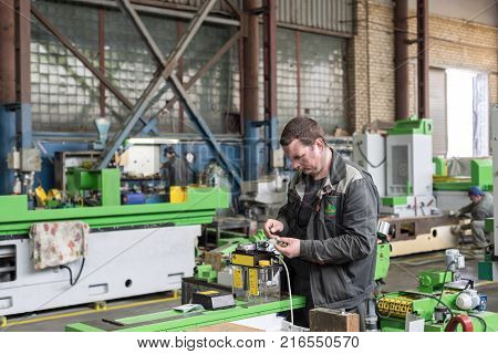 Lipetsk, Russia - June 15, 2017: Lipetsk Machine Tool Plant. The electrician assembles electrical assemblies. Works on assembling the electrical circuit of a metal-cutting machine.