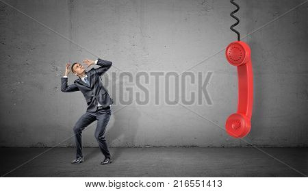 A small scared businessman on concrete background near a large red retro phone handle hanging down. Communications officer. Talking to clients. Negative feedback.