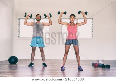 Fitness fit people training arms at gym doing overhead shoulder press with dumbbells weights or standing dumbbell press exercise. Asian woman and Caucasian man couple .