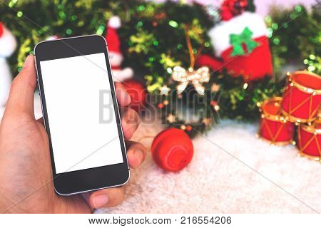 Mockup image of a hand holding black mobile phone with blank white screen with christmas decorations background