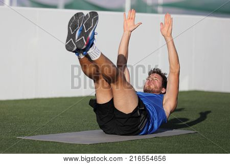 Abs exercise leg lift toe touch sit-up workout man strength training at fitness gym athletic stadium. Athlete working out crunches exercises for stomach muscles and weight loss.