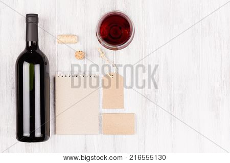 Corporate identity template for wine industry with bottle red wine and wineglass on soft white wood background. Mock up for branding advertising design business presentations and portfolios.