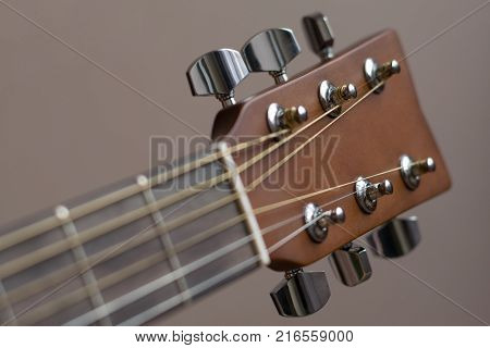 Headstock with tune machine head of acoustic six-string guitar close-up.