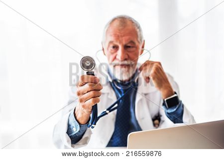 Senior male doctor with laptop at the office desk, holding a stethoscope.