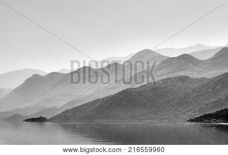 Misty mountains with wavy peaks over the water, lake Skadar in Montenegro